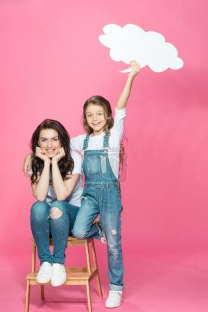 Photo for Beautiful happy mother and daughter with blank speech bubble posing on stool isolated on pink - Royalty Free Image