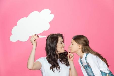 Photo pour Smiling mother and daughter with blank speech bubble gesturing for silence isolated on pink - image libre de droit