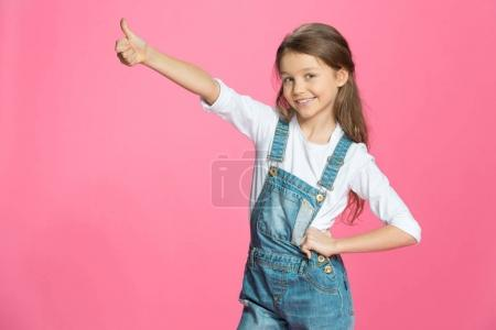 Photo for Beautiful smiling little girl in denim overalls showing thumb up isolated on pink - Royalty Free Image