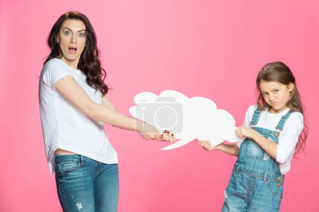 Photo for Emotional mother and daughter pulling blank speech bubble isolated on pink - Royalty Free Image