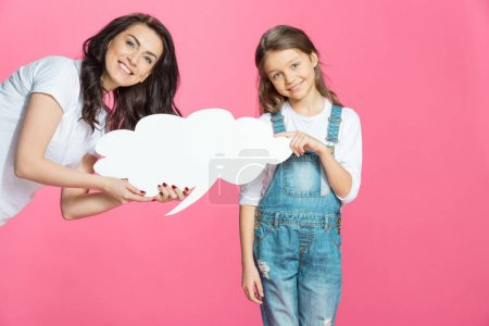 Photo pour Beautiful smiling mother and daughter holding blank speech bubble isolated on pink - image libre de droit