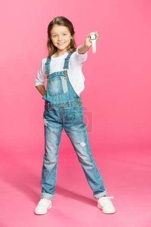 Photo pour Adorable petite fille en salopette denim tenant smartwatch et souriant isolé sur rose - image libre de droit