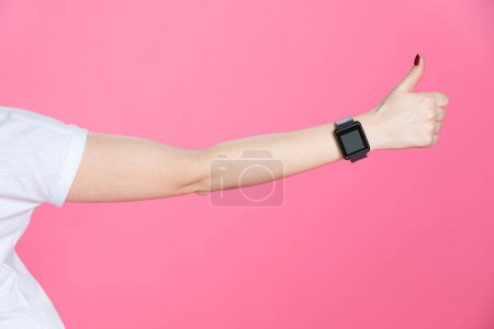 Woman with smartwatch showing thumb up