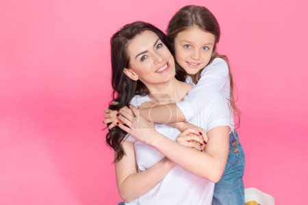 Photo for Happy beautiful mother and daughter sitting together and hugging isolated on pink - Royalty Free Image