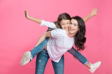 Photo for Happy mother piggybacking adorable little daughter smiling at camera isolated on pink - Royalty Free Image