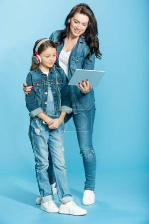 Photo for Happy mother and daughter in headphones using digital tablet in studio isolated on blue - Royalty Free Image