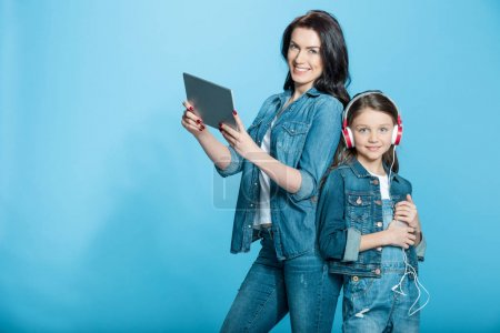 Photo for Happy mother and daughter in headphones using digital tablet and smartphone in studio isolated on blue - Royalty Free Image