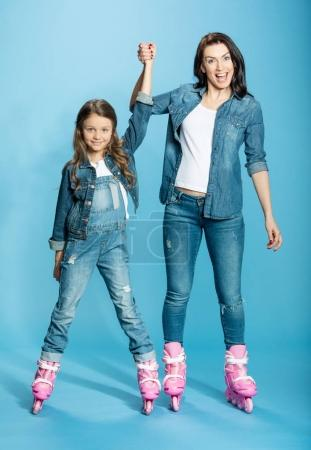 Photo for Mother and daughter in roller skates holding hands in studio isolated on blue - Royalty Free Image