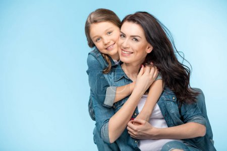 Photo for Portrait of happy mother and daughter hugging in studio isolated on blue - Royalty Free Image