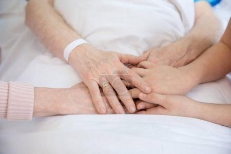 grandmother and grandfather holding hands with patient