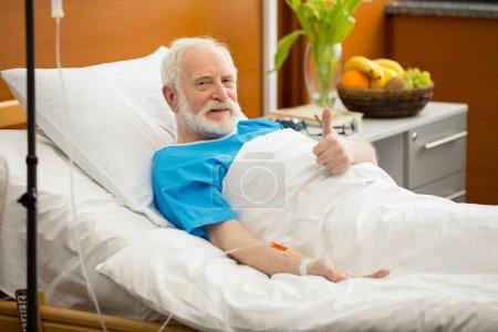 Photo pour Patiente âgée souriante allongée dans un lit d'hôpital et montrant le pouce levé - image libre de droit