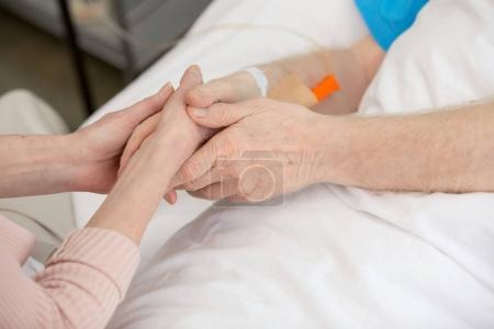 Wife with senior man in hospital
