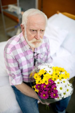 Photo for Upset senior man with bouquet sitting on hospital bed and looking away - Royalty Free Image