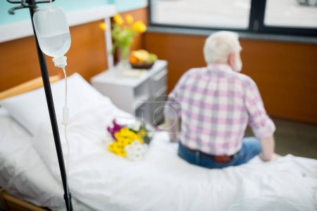 Senior man with flowers in hospital