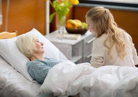 Photo pour Vue latérale de la grand-mère de malades visite fille couché dans son lit d'hôpital - image libre de droit