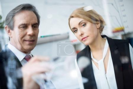 Photo pour Homme d'affaires concentré et femme d'affaires écrivant et discutant graphique d'affaires - image libre de droit