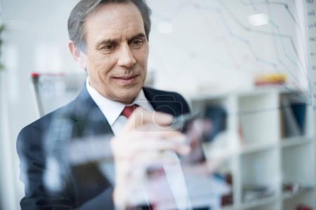 Foto de Sonriente hombre de negocios maduro con lápiz escribir gráfico de negocio en el tablero de cristal - Imagen libre de derechos
