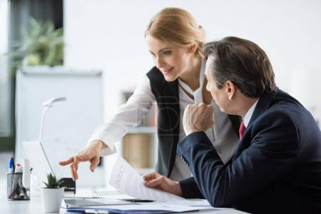Photo for Businessman looking at smiling blonde businesswoman pointing at laptop - Royalty Free Image
