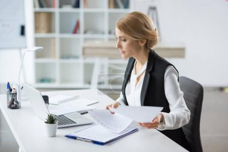 Photo for Attractive blonde businesswoman holding documents and using laptop at workplace - Royalty Free Image
