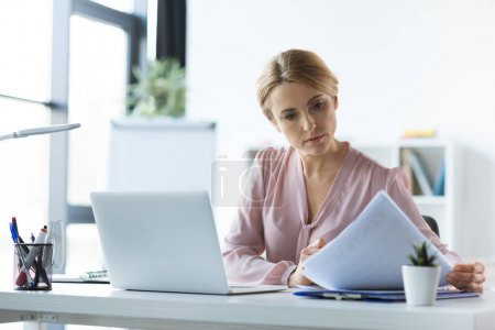 Photo pour Femme d'affaires grave avec ordinateur portable et documents de travail au bureau - image libre de droit