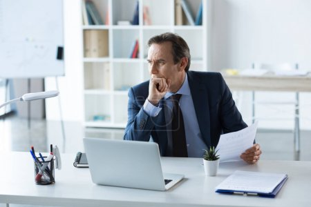 Photo for Mature pensive businessman with laptop and documents working in office - Royalty Free Image
