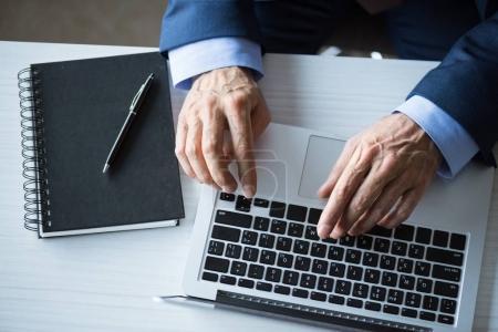 Photo pour Vue recadrée de l'homme d'affaires tapant sur ordinateur portable sur le lieu de travail dans le bureau - image libre de droit