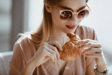 Photo for Attractive caucasian girl in sunglasses with croissant in cafe, having lunch concept - Royalty Free Image