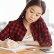 Attractive asian student writing in diary and sitt...