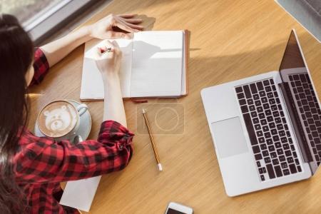 Photo pour Plan recadré d'une jeune femme assise à table avec café et ordinateur portable et écrivant dans un cahier - image libre de droit