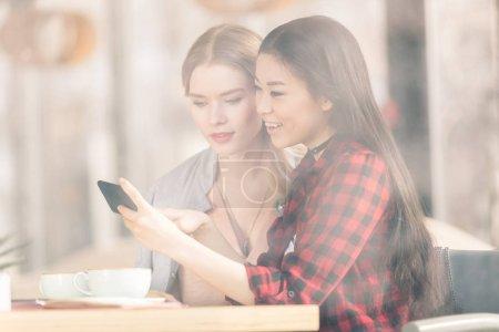 Photo pour Sourire des jeunes femmes à l'aide de smartphone tout en buvant du café ensemble au déjeuner de travail - image libre de droit