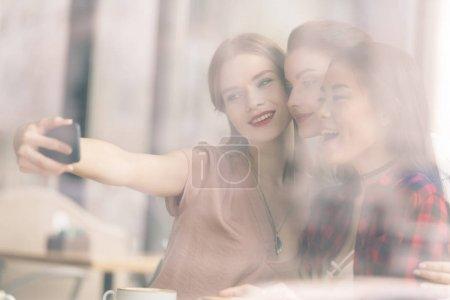 Foto de Vista lateral de amigos felices que juntos selfie en café - Imagen libre de derechos