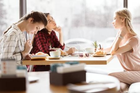 Photo pour Vue de côté du groupe d'amis étudier ensemble dans le café - image libre de droit