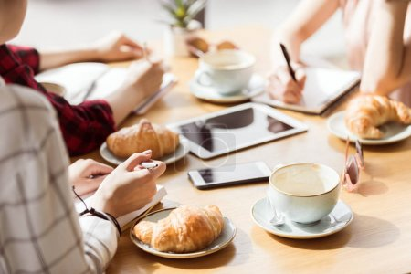 Photo pour Vue partielle du groupe d'amis étudier ensemble dans le café - image libre de droit