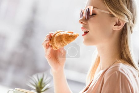young woman eating croissant