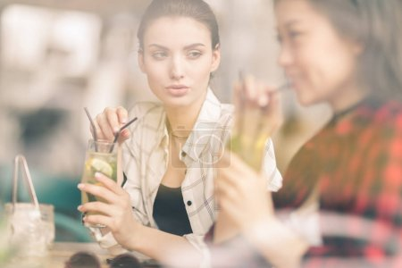 girls drinking cocktails in cafe