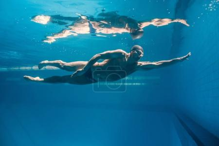 Photo for Underwater picture of young swimmer in goggles exercising in swimming pool - Royalty Free Image