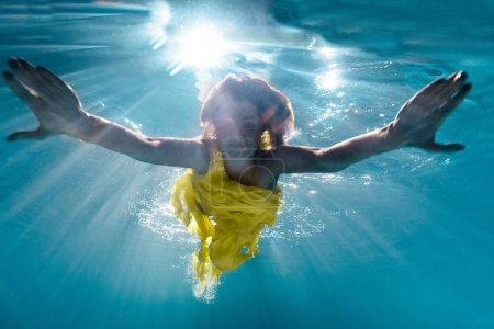 Photo for Underwater picture of beautiful young woman in dress swimming in swimming pool - Royalty Free Image