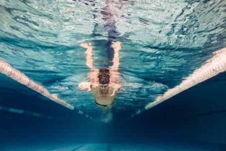 Photo pour Photo sous-marine de jeune nageur en casquette et lunettes de formation dans la piscine - image libre de droit