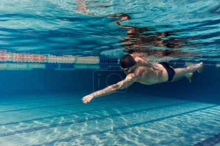 underwater picture of young swimmer in cap and goggles training in swimming pool