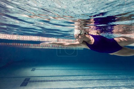 Photo for Underwater picture of young female swimmer exercising in swimming pool - Royalty Free Image