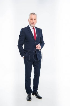 Photo for Full length portrait of handsome mature businessman in suit looking at camera isolated on white - Royalty Free Image