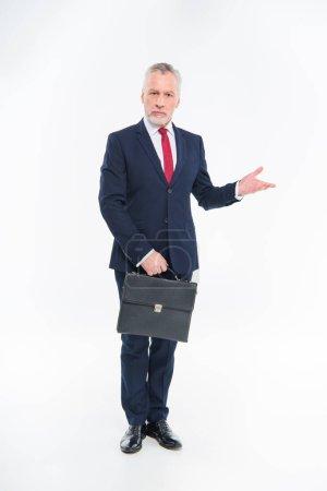 Foto de Mature businessman holding briefcase and gesturing with hand isolated on white - Imagen libre de derechos