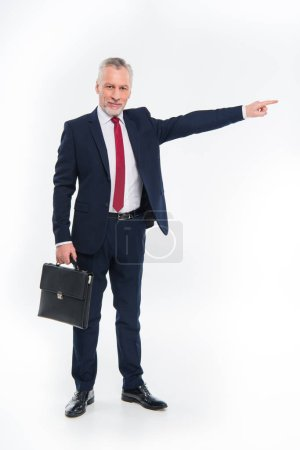Photo for Smiling businessman holding briefcase and pointing away isolated on white - Royalty Free Image