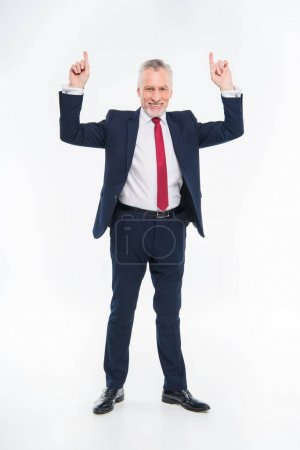 Smiling businessman pointing up
