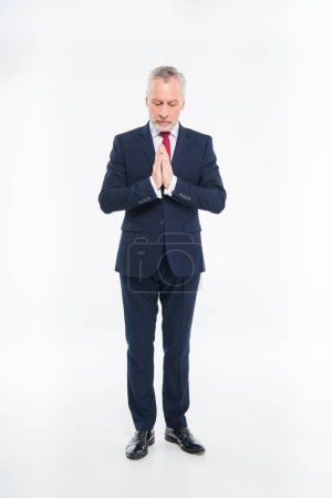 Mature businessman praying