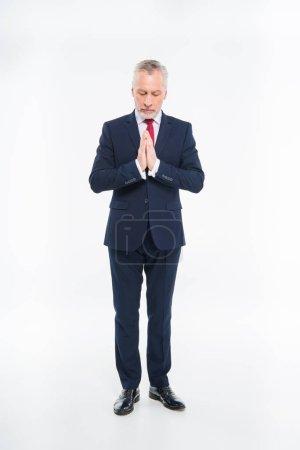 Photo pour Portrait complet d'homme d'affaires mature priant isolé sur blanc - image libre de droit