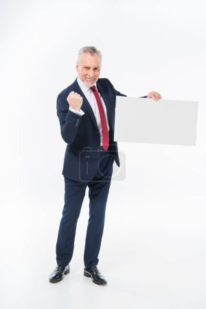 Photo for Excited mature businessman triumphing and holding blank white card isolated on white - Royalty Free Image