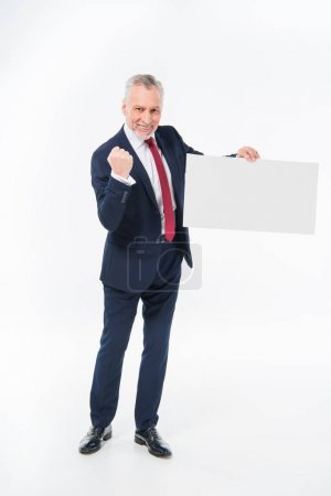 Foto de Excited mature businessman triumphing and holding blank white card isolated on white - Imagen libre de derechos