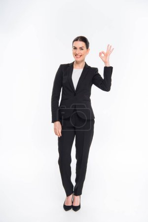 Photo for Smiling businesswoman showing OK sign and looking at camera isolated on white - Royalty Free Image