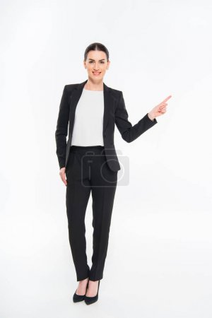 Photo for Smiling businesswoman pointing with finger and looking at camera isolated on white - Royalty Free Image